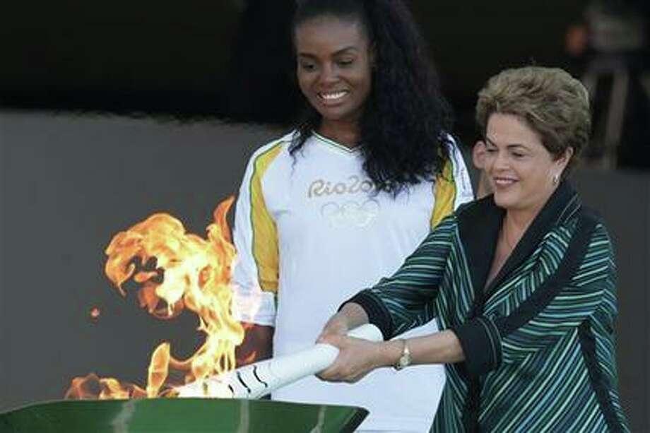 La presidenta brasileña Dilma Rousseff, derecha, enciende la antorcha olímpica al lado de la voleibolista Fabiana Claudino durante una ceremonia tras la llegada de la llama olímpica a Brasil el martes, 3 de mayo de 2016, en Brasilia.  (AP Photo/Eraldo Peres) Photo: AP