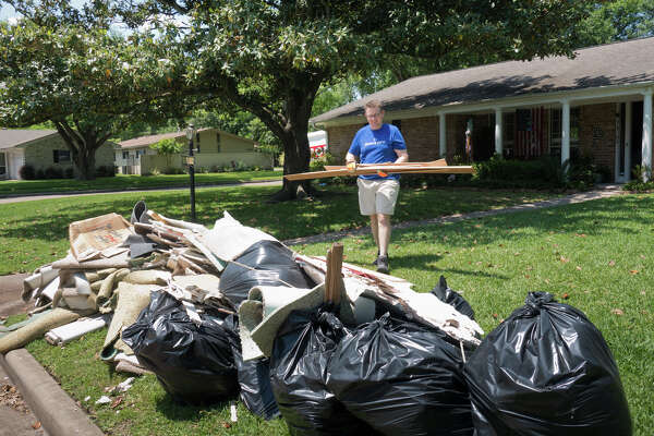 Stephen Price stacks debris in his front yard for pickup. The Price home in West Houston has flooded three times in recent years, and the family faces tough decisions on what to do.