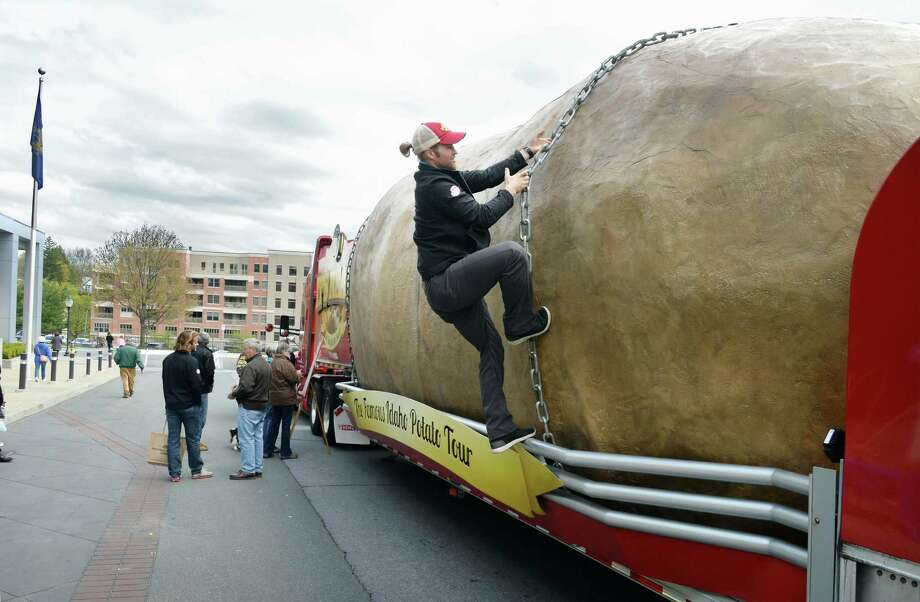Potato ambassador Adam Branstetter climbs up the Big Idaho Potato Truck, 72 feet long and hauling a 12,000 pound replica Idaho Potato around the country as part of The Famous Idaho Potato Tour, during its stop at the Saratoga Springs City Center Tuesday May 3, 2016 in Saratoga Springs, NY.  (John Carl D'Annibale / Times Union) Photo: John Carl D'Annibale / 20036459A