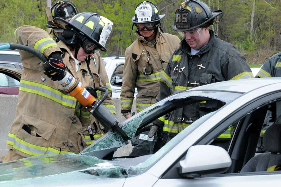 Troy Deputy Mayor Monica Kurzejeski, left, uses the Jaws of Life to take a roof of a car off during a extraction exercise as part of Fire-Ops 101 a hands-on simulation of firefighting techniques and first-response situations on Tuesday May 3, 2016 in Latham , N.Y. Under the supervision of professional firefighters, local and state elected officials took part. (Michael P. Farrell/Times Union) Photo: Michael P. Farrell / 20036441A