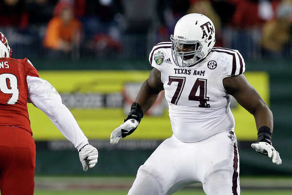 Texas A&M offensive lineman Germain Ifedi (74) plays against Louisville linebacker James Hearns (99) in the second half of the Music City Bowl NCAA college football game Wednesday, Dec. 30, 2015, in Nashville, Tenn. Louisville won 27-21. (AP Photo/Mark Humphrey)