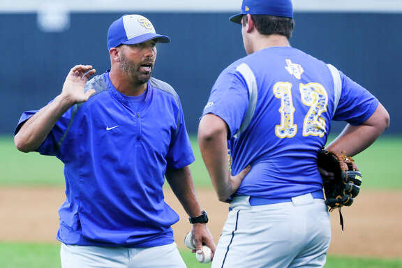 Clemens head coach Russell Doege (left) talks to starting pitcher Cody Sasser during their District 25-6A game at Smithson Valley on April 19, 2016.