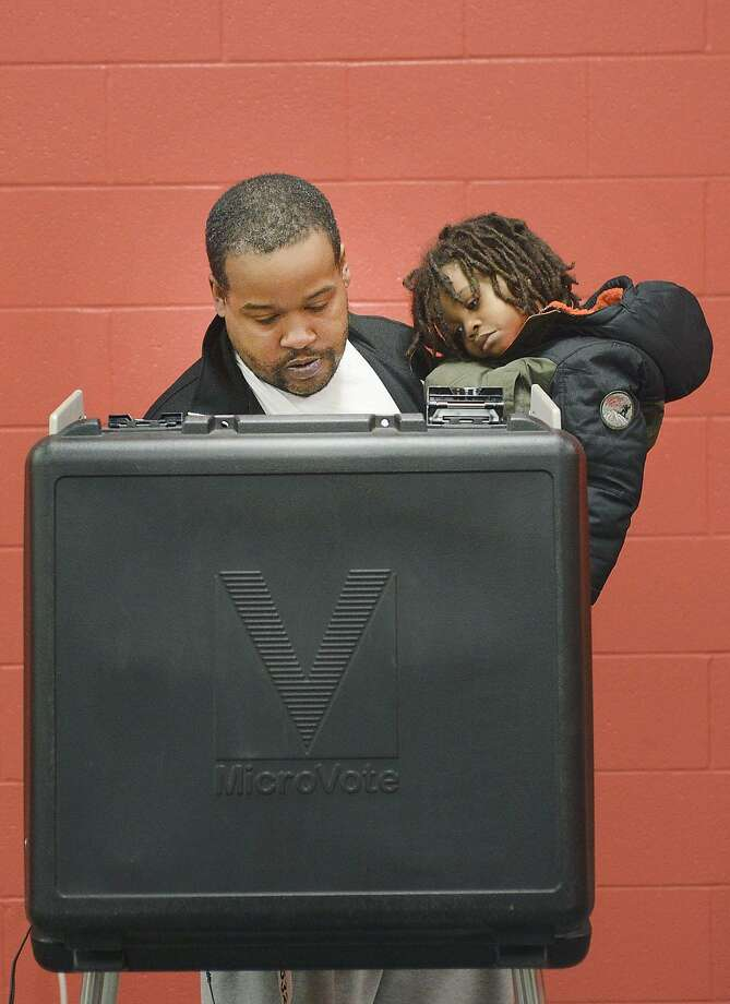Greg Moore holds his son Quendell as he votes in Indiana's primary election at a community center in Fort Wayne. Photo: Samuel Hoffman, Associated Press