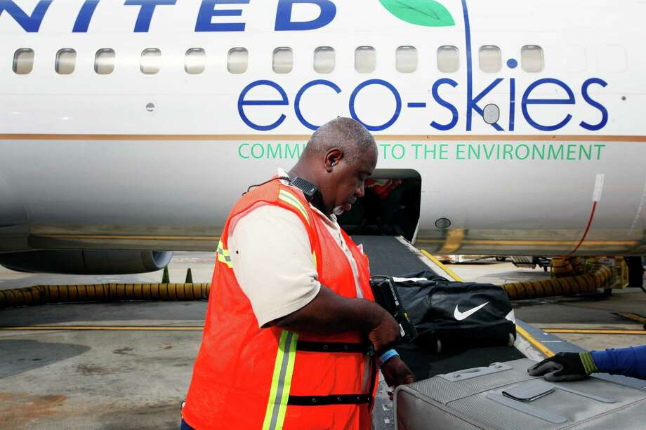 United Airlines crew member, Charles Keys, scans the checked bags of passengers as they are loaded into the belly of the aircraft, prior to the first US commercial flight powered by advanced biofuel, Monday, November 7, 2011 at George Bush Intercontinental Airport in Houston, Texas. The Boeing 737 departed terminal E at 10:30am and was bound for Chicago O'Hare International Airport. (Todd Spoth / For The Chronicle) Photo: TODD SPOTH, Photographer / ONLINE_YES