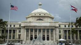 A Puerto Rican and an American flag fly outside the Capitol of Puerto Rico, home to the Senate and House of Representatives, in San Juan, Puerto Rico, on Sunday. Puerto Rico will default on a $422 million bond payment for its Government Development Bank.
