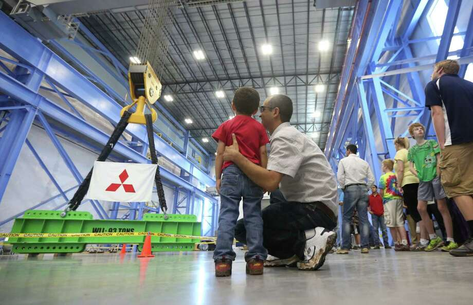 Parsa Hosseini, 3, listens to his father Alireza Hosseini, 37,  while viewing the largest overhead crane installed in North America in the last couple of years while touring the Mitsubishi Heavy Industries Compressor International Corp production facility on Saturday, April 25, 2015, in Pearland. ( Mayra Beltran / Houston Chronicle ) Photo: Mayra Beltran, Staff / © 2015 Houston Chronicle