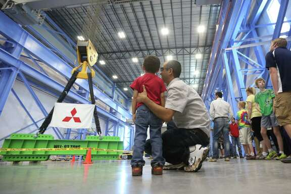 Parsa Hosseini, 3, listens to his father Alireza Hosseini, 37,  while viewing the largest overhead crane installed in North America in the last couple of years while touring the Mitsubishi Heavy Industries Compressor International Corp production facility on Saturday, April 25, 2015, in Pearland. ( Mayra Beltran / Houston Chronicle )