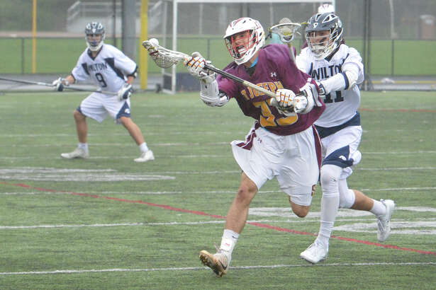 St Joes #33 Kevin Trefz keeps the ball away from Wiltons #11 Michael Brown during St Joes at Wilton Boys Lacrosse in Wilton Conn. May 3    2016
