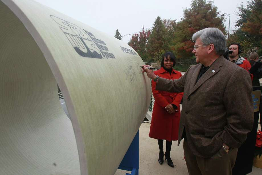 San Antonio Water System board chairman Berto Guerra signs a 54-inch diameter pipe in December 2014 when the utility completed a deal to buy water from a private company sent via a pipeline from Burleson County. Photo: John Davenport /San Antonio Express-News / ©San Antonio Express-News