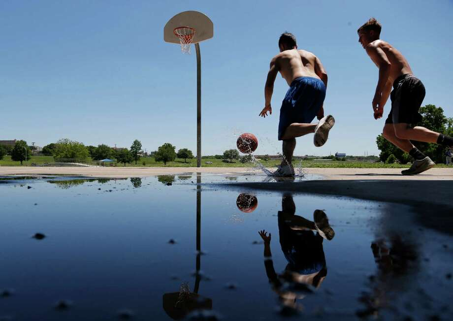 Desmond Waters and Daniel Gandy work around puddles left by recent rains to play basketball in Trinity Park as sun and spring weather return to Tarrant County and North Texas, Tuesday, May 3, 2016. (Rodger Mallison/Star-Telegram via AP) MANDATORY CREDIT Photo: Rodger Mallison, MBI / Star-Telegram