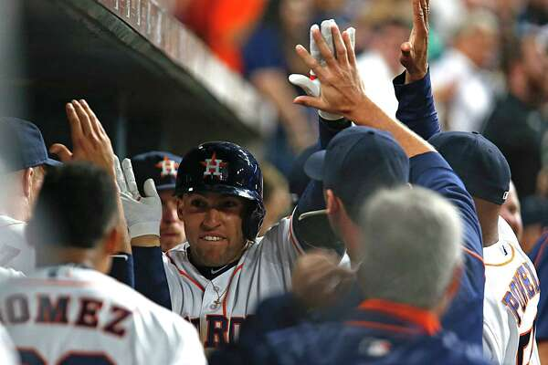 Houston Astros right fielder George Springer center, high fives teammates after hitting a home run against the Minnesota Twins during the fourth inning of MLB game action at Minute Maid Park Tuesday, May 3, 2016, in Houston.