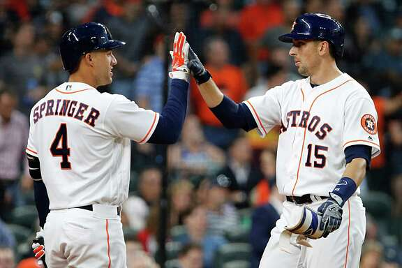 Houston Astros catcher Jason Castro left, high fives Astros right fielder George Springer left, after hitting a home run during the third inning of MLB game action at Minute Maid Park Tuesday, May 3, 2016, in Houston.