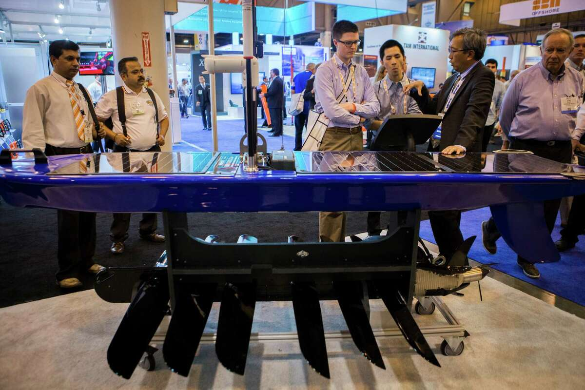 Amol Pawar, left, Chetan Khutale, Richard Purvis and Justin Yip take a look at the Wave Glider SV3 on Tuesday at the Schlumberger booth during the Offshore Technology Conference. Explaining how it works is Schlumberger's Benny Poedjono.