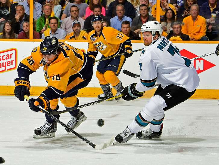 NASHVILLE, TN - MAY 03:  James Neal #18 of the Nashville Predators fights Paul Martin #7 of the San Jose Sharks for a loose puck during the first period of Game Three of the Western Conference Second Round during the 2016 NHL Stanley Cup Playoffs at Bridgestone Arena on May 3, 2016 in Nashville, Tennessee.  (Photo by Frederick Breedon/Getty Images)