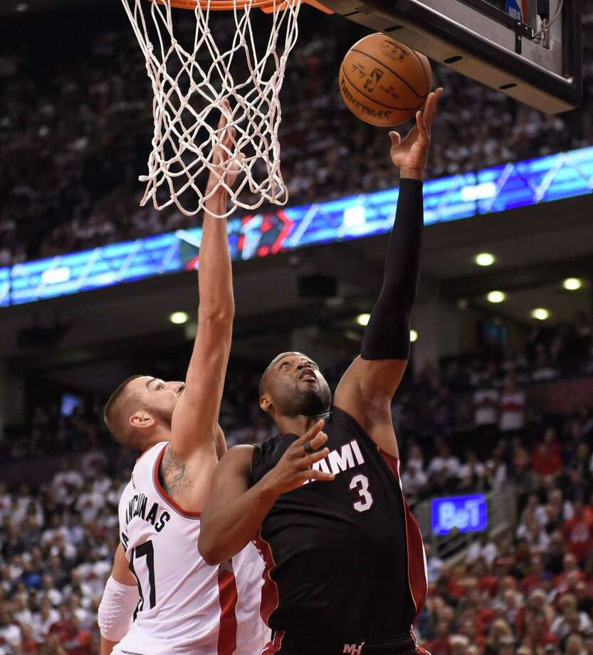Toronto Raptors' Jonas Valanciunas defends as Miami Heat's Dwyane Wade (3) shoots during the second half in Game 1 of a second-round NBA basketball playoff series, Tuesday, May 3, 2016 in Toronto. (Frank Gunn/The Canadian Press via AP) MANDATORY CREDIT ORG XMIT: FNG324 Photo: Frank Gunn / CP