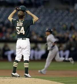 Oakland Athletics' Sonny Gray (54) removes his cap as he waits for Seattle Mariners' Leonys Martin, right, to run the bases after hitting a two run home run in the third inning of a baseball game Tuesday, May 3, 2016, in Oakland, Calif. (AP Photo/Ben Margot)