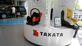 Visitors look at a Toyota's Estima near child seats, manufactured and displayed by Takata Corp. at an automaker's showroom in Tokyo. U.S. officials are expected to announce the recall of as much as 35 million more Takata airbags as early as Wednesday. The air bags can unexpectedly explode, sending metal parts hurtling into the cabin. At least 11 deaths worldwide have been linked to the defect.