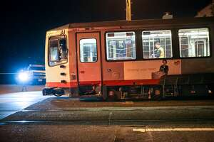 SFMTA officials investigate an L-Taraval Muni train which was hit by a car at the corner of 14th Avenue and Ulloa Street, Friday, Jan. 23, 2015, in San Francisco, Calif.