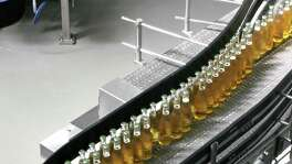Bottles of beer move down a conveyor at the Anheuser-Busch brewery in St. Louis. Anheuser-Busch InBev said one of its top markets, Brazil, had its most challenging quarter in many years. But it reiterated its forecast for net revenue in the country to grow by mid-to-high single digits for the year, helped in part by the summer Olympics in Rio de Janeiro.