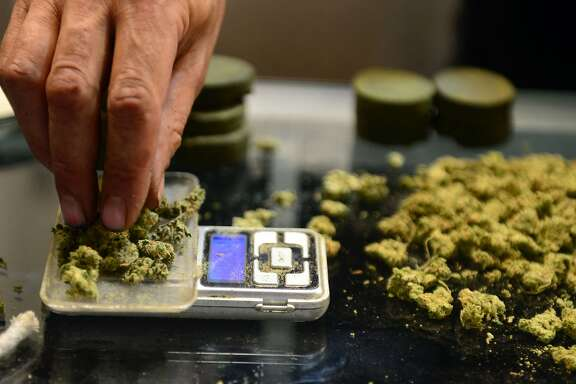 (FILES) This file photo taken on July 04, 2014 shows a vendor weighing buds for card-carrying medical marijuana patients attending Los Angeles' first-ever cannabis farmer's market at the West Coast Collective medical marijuana dispensary, on the fourth of July, or Independence Day, in Los Angeles, California.  Germany is to legalise cannabis for medicinal purposes early next year, according to the Health minister who will present draft legislation to the German cabinet on May 4, 2016 / AFP PHOTO / STFSTF/AFP/Getty Images
