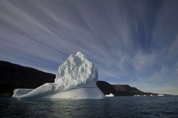 FILE - In this July 21, 2011 file photo, an iceberg floats in the sea near Qeqertarsuaq, Disko Island, Greenland. Global warming is shifting the way the Earth wobbles on its polar axis, a new NASA study finds. Melting ice sheets, especially in Greenland, are changing the distribution of weight on Earth. And that has caused both the North Pole and the wobble, which is called polar motion, to change course, according to a study published Friday, April 8, 2016, in the journal Science Advances.  (AP Photo/Brennan Linsley, File)