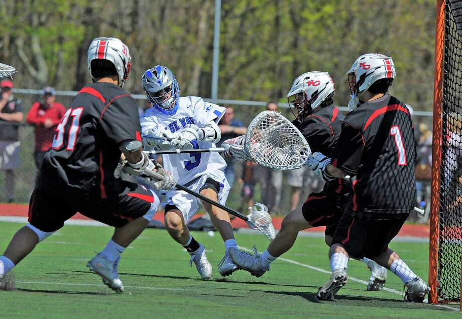Darien's Colin Minicus sneaks a shot past New Canaan goalie Drew Morris during Saturday's 10-7 home win. Photo: Matthew Brown / Hearst Connecticut Media / Stamford Advocate