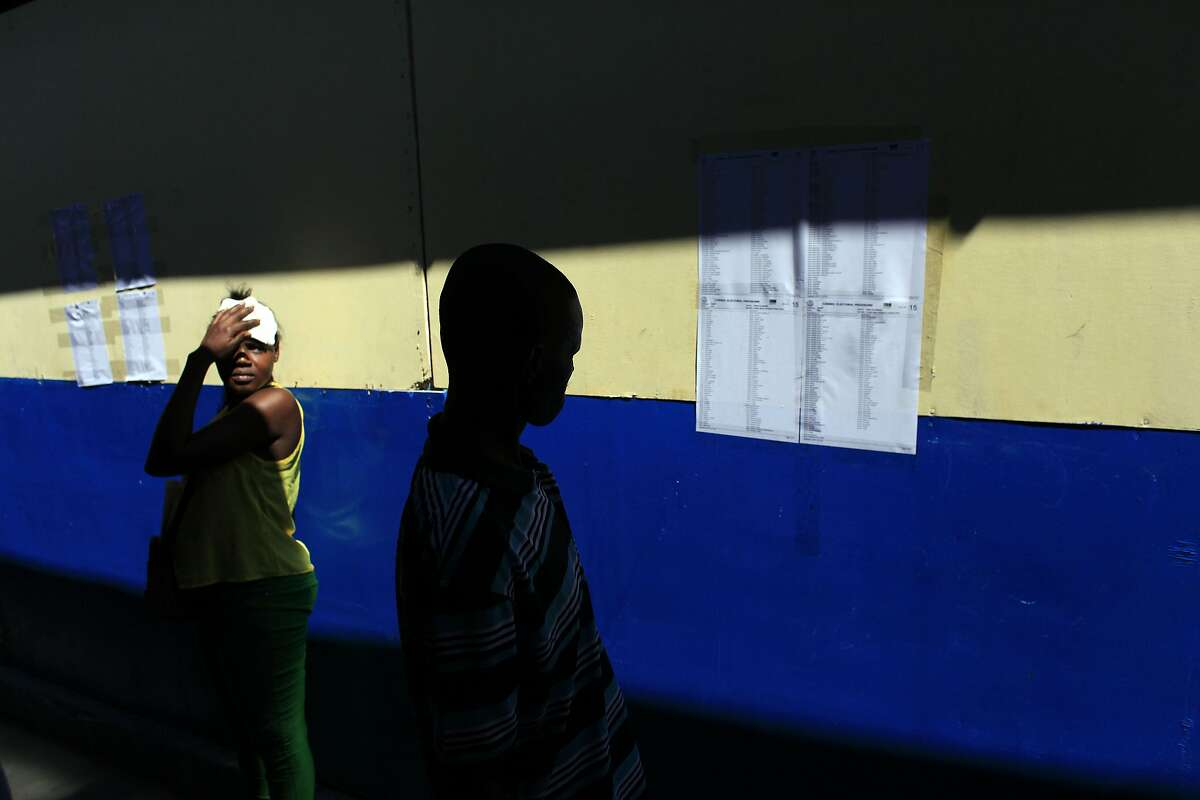 FILE - In this Oct. 25, 2015, file photo, a voter looks for his name on a voters lists during elections in Port-au-Prince, Haiti. Worried by Haiti�s partisan tensions, the OAS says it�s critical that elections resume without repeating the issues or problems of the recent past. (AP Photo/Ricardo Arduengo, File)
