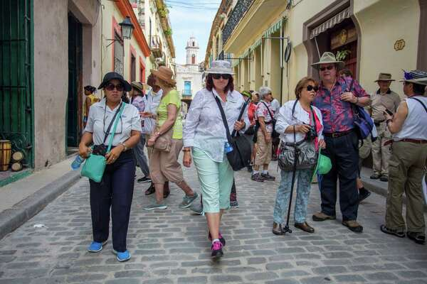 SmarTours Tour Director Pamela Boudrot, center, and local tour guide Enedis Tamayo, left, lead their group of tourists in Havana, Cuba, last month.