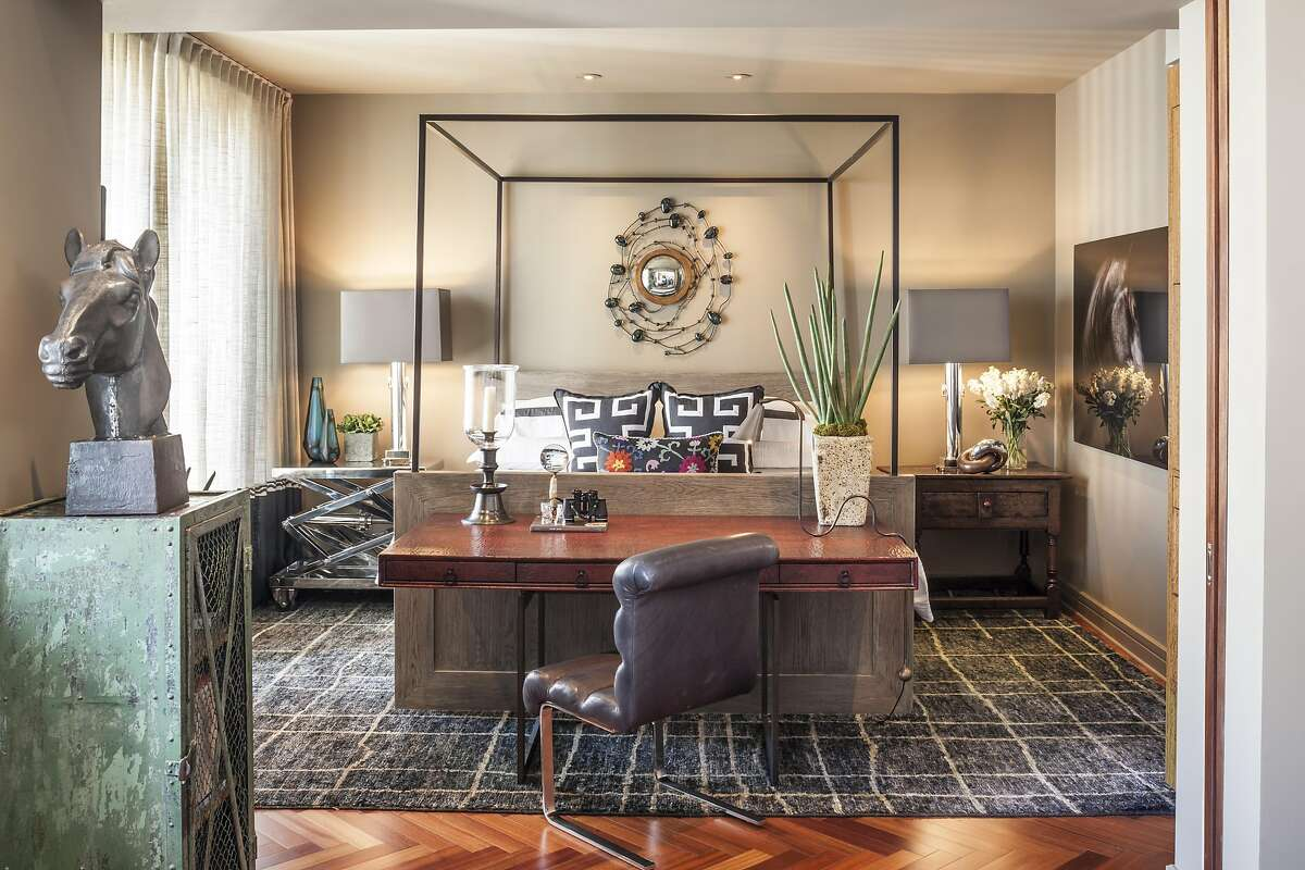 In the apartment�s one bedroom, a custom desk at the foot of the bed makes shrewd use of the small space.