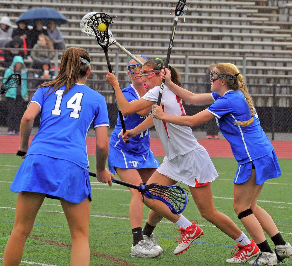 Greenwich's Genevieve DeWinter pushes through Darien defenders during the Cardinals' 16-6 loss on Tuesday at Cardinal Stadium.