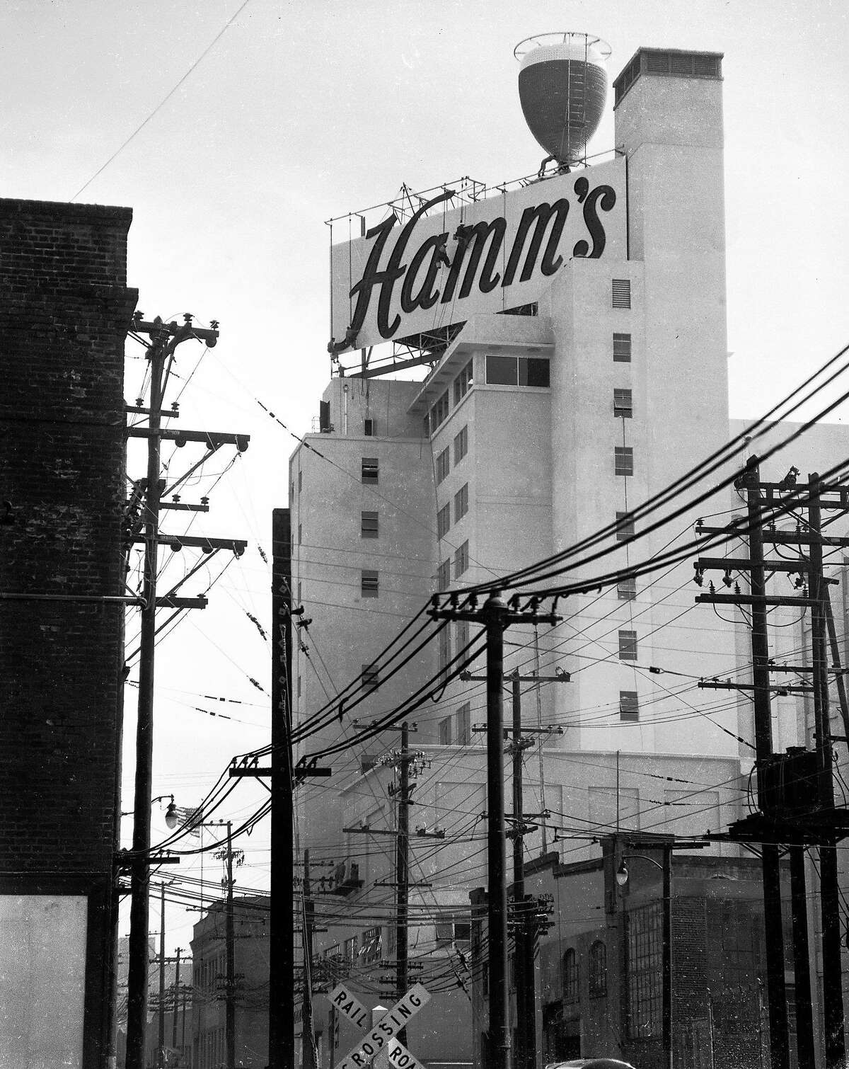 """June 24, 1954: If you were a kid in the 1950s, 1960s or 1970s, this Hamm's Brewery sign at 1550 Bryant Street was likely your happy place. The chalice at the top had neon lights that made the glass look like it was """"filling up"""" with beer at night, visible from the Central Freeway on the way to Noe Valley, the Castro and beyond. This photo was taken in 1954, when the Hamm's chalice was replacing the Rainier Brewery sign. (Look closely, and you can see workers on scaffolding.) Longtime Chronicle photographer Bob Campbell, an overseas photographer during World War II, was sent to take photos of the new sign - and took six from different angles throughout the city. The Hamm's sign was taken down in 1975."""