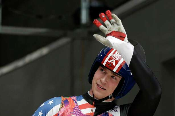 Tucker West of the United States waves to supporters in the finish area during the men's singles luge final at the 2014 Winter Olympics, Sunday, Feb. 9, 2014, in Krasnaya Polyana, Russia. (AP Photo/Natacha Pisarenko)