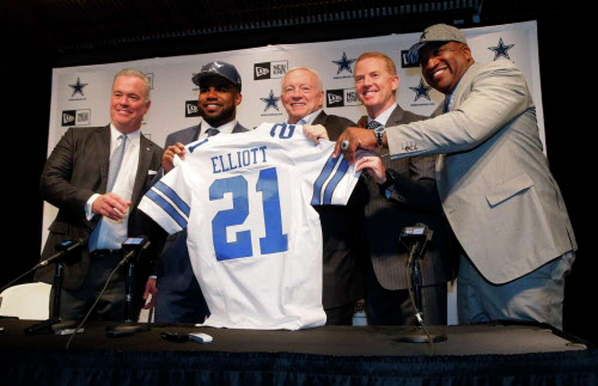 The Dallas Cowboys NFL football first round draft pick Ezekiel Elliott, second from left, poses for photos with his new jersey and Director of Player Personnel Stephen Jones, from left, team owner Jerry Jones, center, head coach Jason Garrett and Elliott's father Stacy, right, after a news conference at the team's training facility, Friday, April 29, 2016, in Irving, Texas. (AP Photo/Tony Gutierrez)