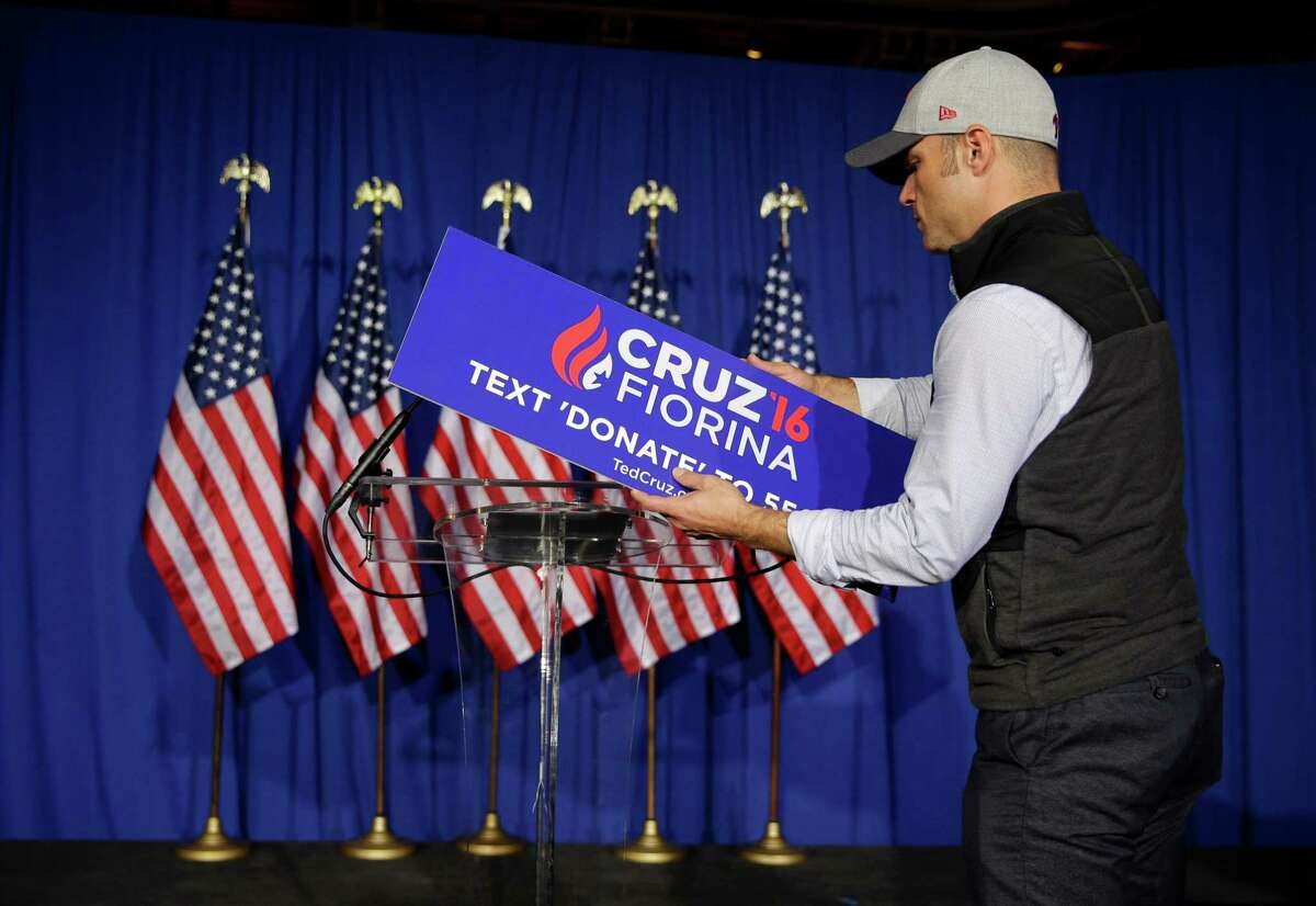 A worker for Republican presidential candidate Sen. Ted Cruz, R-Texas, removes the campaign sign from the podium following primary night campaign event in Indianapolis, Tuesday, May 3, 2016. Cruz ended his presidential campaign, eliminating the biggest impediment to Donald Trump's march to the Republican nomination.