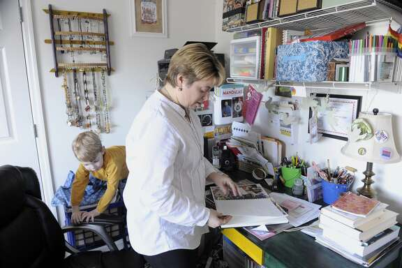 Ledger  flips through some of her coloring books in her home office as one of  her sons, Griffin, plays in their condo.