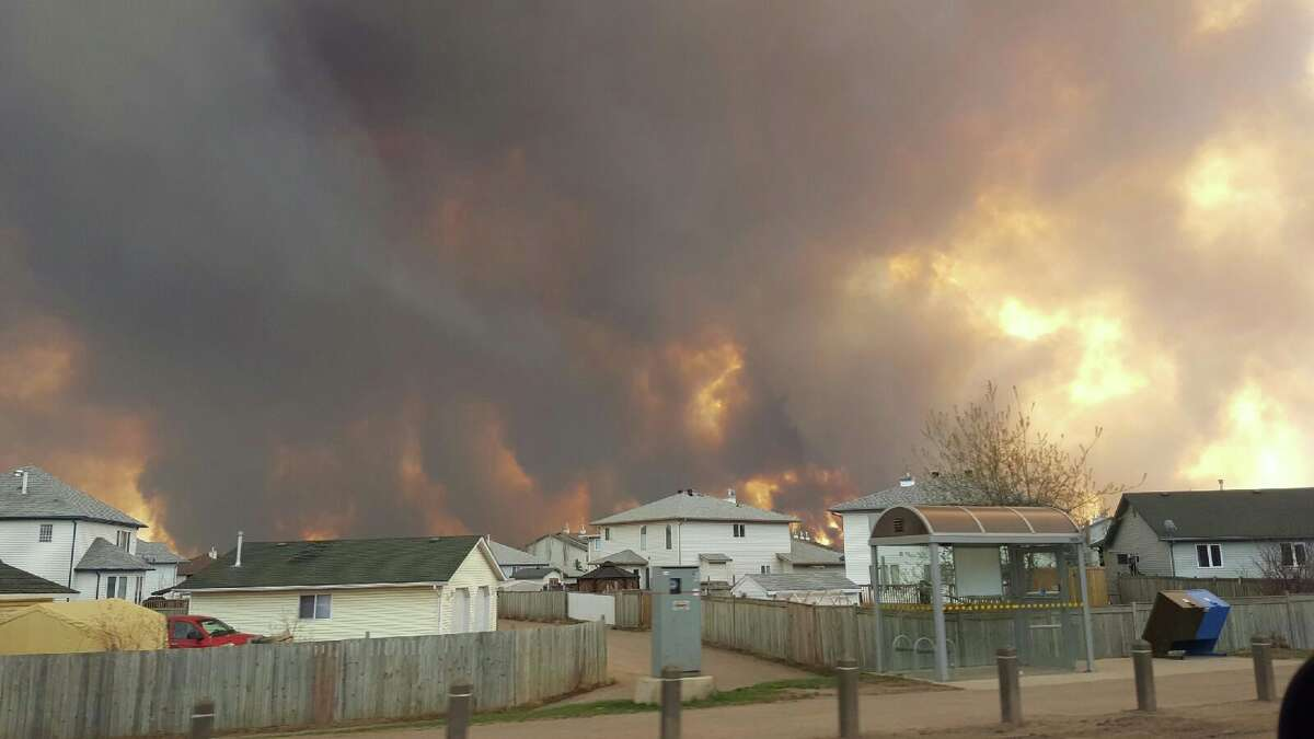 Smoke rises from a wildfire outside of Fort McMurray, Alberta, Tuesday, May 3, 2016. The entire population of the Canadian oil sands city of Fort McMurray, has been ordered to evacuate as a wildfire whipped by winds engulfed homes and sent ash raining down on residents. (Mary Anne Sexsmith-Segato/The Canadian Press via AP) MANDATORY CREDIT ORG XMIT: CPT504