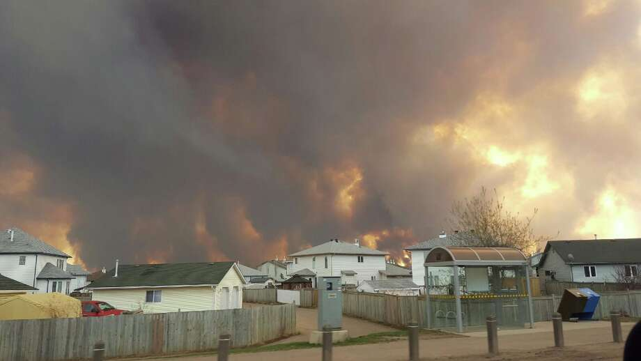 Smoke rises from a wildfire outside of Fort McMurray, Alberta, Tuesday, May 3, 2016. The entire population of the Canadian oil sands city of Fort McMurray, has been ordered to evacuate as a wildfire whipped by winds engulfed homes and sent ash raining down on residents. (Mary Anne Sexsmith-Segato/The Canadian Press via AP) MANDATORY CREDIT ORG XMIT: CPT504 Photo: Mary Anne Sexsmith-Segato / The Canadian Press