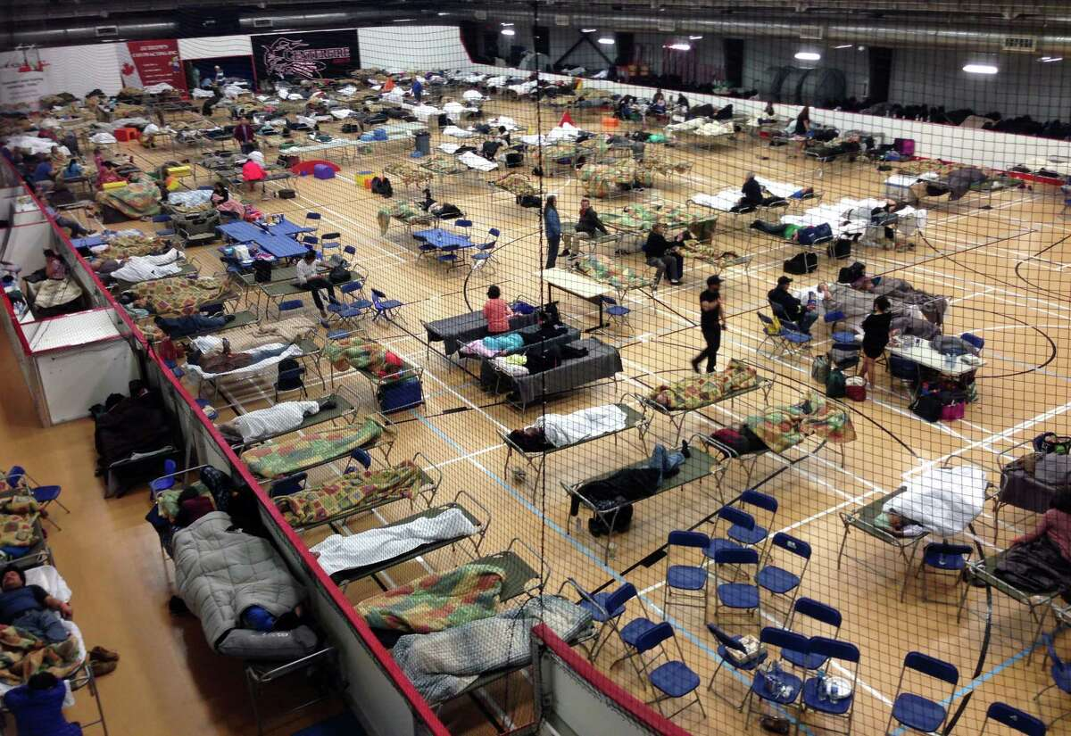 Cots are set up on the gym floor at an evacuee reception center, operated by the regional municipality of Wood Buffalo in Anzac, Alberta, Canada on Wednesday, May 4, 2016. More than 80,000 residents were ordered to flee the Canadian oil sands city of Fort McMurray, as a wildfire moved into the city, destroying whole neighborhoods. (Mike Allen/The Canadian Press via AP) MANDATORY CREDIT ORG XMIT: EDMX101