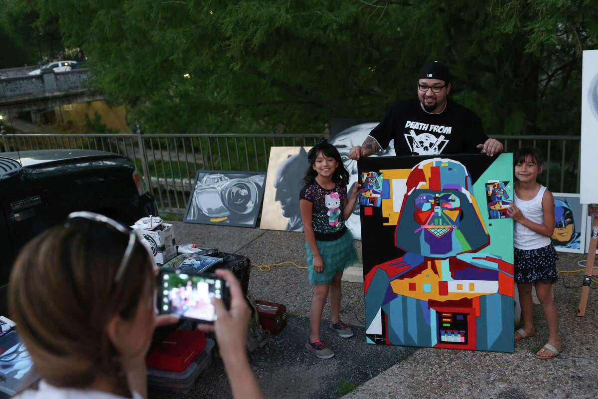 Arlene Cavazos photographs her daughters, Sunshine Vega, 9, left, and Sky Vega, 8, with artist Adrian De La Cruz and his painting of Darth Vader as fans of