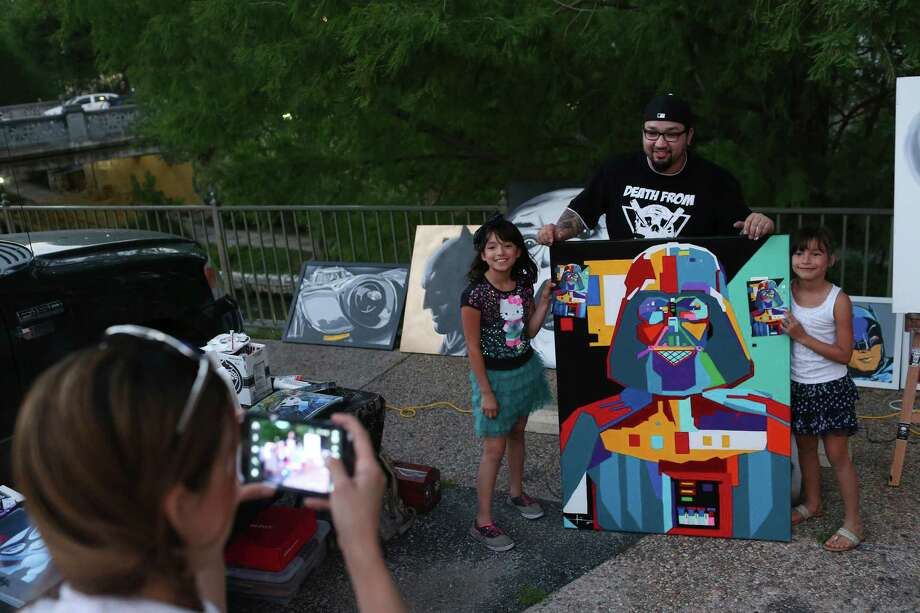 "Arlene Cavazos photographs her daughters, Sunshine Vega, 9, left, and Sky Vega, 8, with artist Adrian De La Cruz and his painting of Darth Vader as fans of ""Star Wars"" fans gather at The Korova to celebrate May the 4th Be With You, Wednesday, May 4, 2016. Fans took on the popular quote in the ""Star Wars,"" movies, May the Force be with you as a reason to celebrate May 4. Photo: JERRY LARA, San Antonio Express-News / © 2016 San Antonio Express-News"