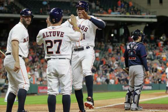 Houston Astros second baseman Jose Altuve (27) and Houston Astros shortstop Carlos Correa (1) celebrates off a two-run double by Houston Astros center fielder Carlos Gomez (30) in the fifth. Photos of game three between Houston Astros and Minnesota Twins on Wednesday, May 4, 2016, in Houston. The series is tied 1-1.