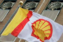 FILE - In this Monday, April 7, 2014 file photo, a flag bearing the company logo of Royal Dutch Shell, flies outside the head office in The Hague, Netherlands. The Anglo-Dutch company said Wednesday May 4, 2016 that profit, adjusted for changes in the value of inventories and excluding one-time items, dropped to $1.55 billion from $3.74 billion in the same period in 2015. (AP Photo/Peter Dejong, File)