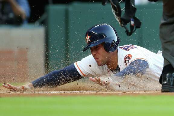 Right fielder George Springer joins the parade of Astros who would cross home plate Wednesday night at Minute Maid Park, scoring on Carlos Correa's double.