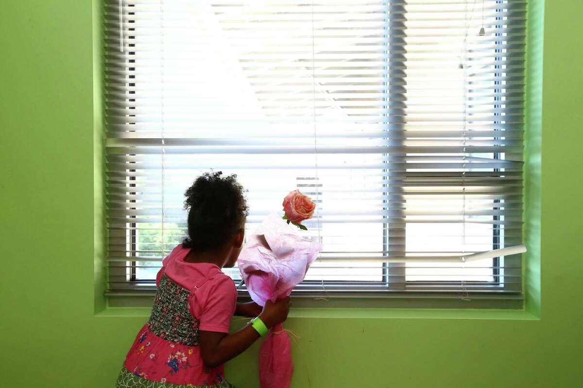 Chloe Daniel-Abbs looks out the window of the Mission's Transitional Living Center, during a Mother's Day celebration, Wednesday, May 4, 2016, in Houston.