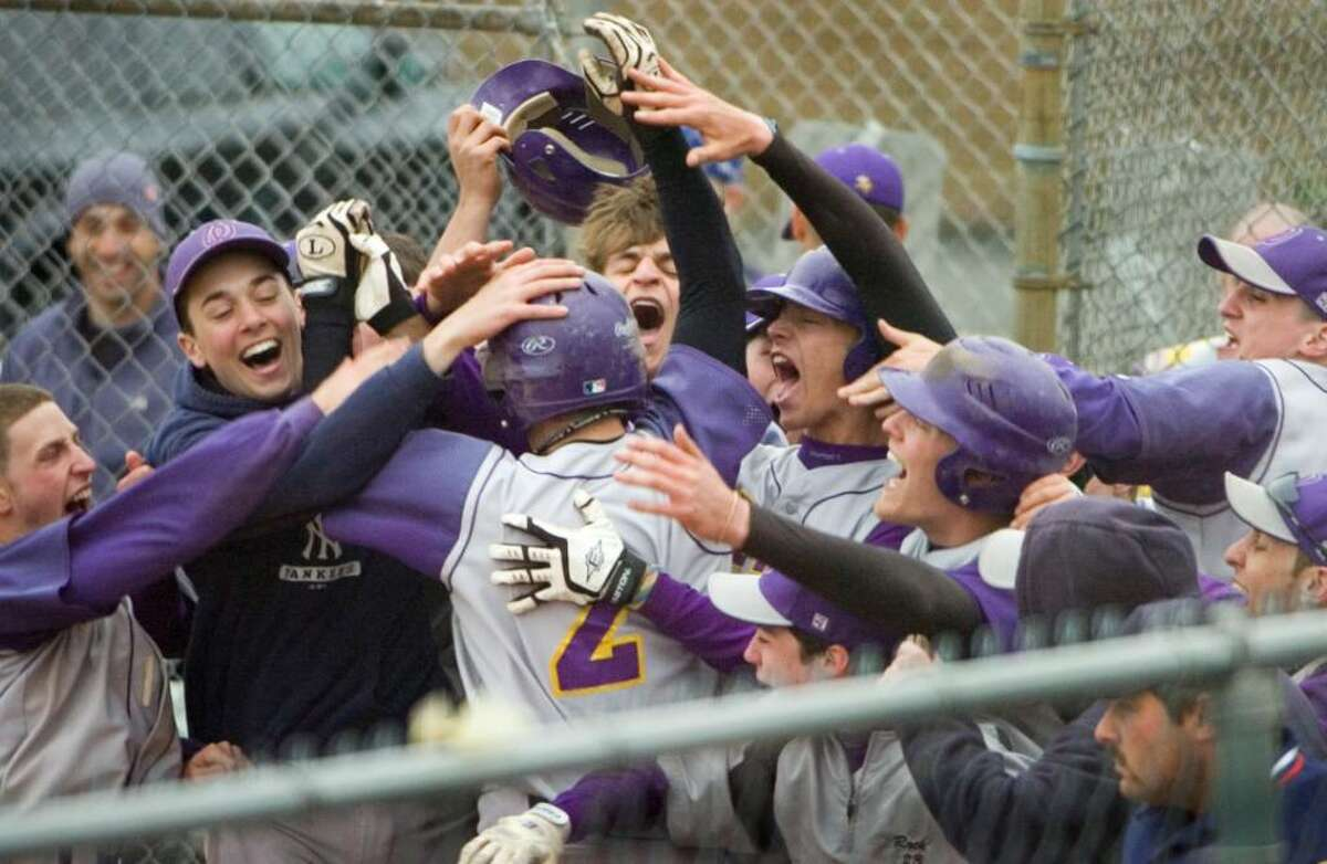 Westhill High School's #2 Tyler Rich is congratulated by the team as he runs across home plate after hitting a grand slam during a boys baseball game against Staples High Schoolin Stamford, Conn on April 16, 2010.