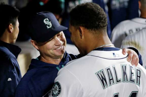 Seattle Mariners manager Scott Servais, left, embraces starting pitcher Taijuan Walker after Walker struck out the Houston Astros side in the seventh inning of a baseball game Monday, April 25, 2016, in Seattle. (AP Photo/Elaine Thompson)