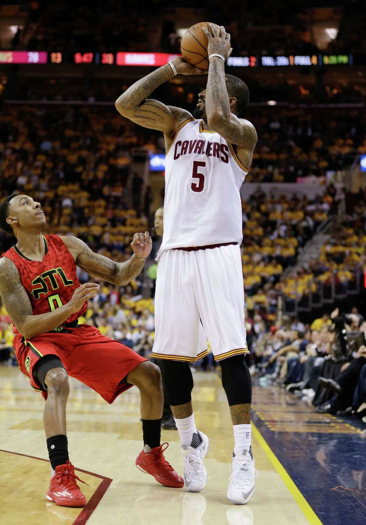 Cleveland Cavaliers guard J.R. Smith (5) puts up a 3-point shot against Atlanta Hawks guard Jeff Teague (0) in the second half during Game 2 of a second-round NBA basketball playoff series, Wednesday, May 4, 2016, in Cleveland. (AP Photo/Tony Dejak)