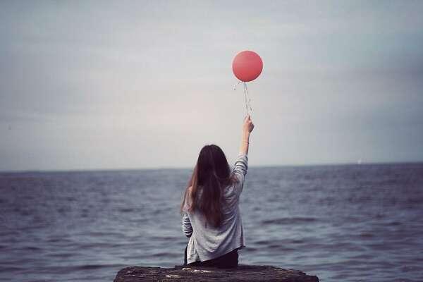 Girl holding balloon at beach
