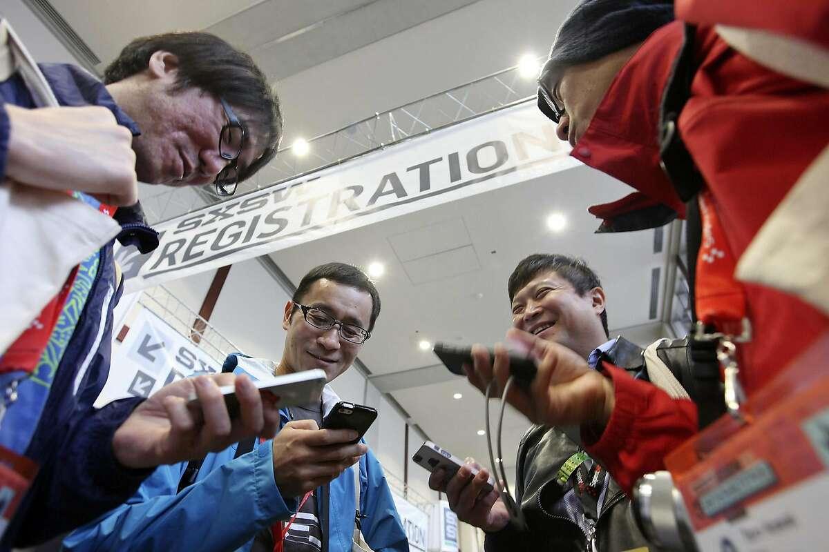 Yahoo Japan employees Kazuhiro Ninomiya (from left), Takamitsu Iriyama, Toshiaki Chiku, and Taro Kawai work on their smart phones at the Austin Convention Center during South by Southwest Friday March 8, 2013 in Austin, TX.