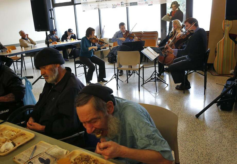 Charles Calderon, 71, front left, and Wayne Marques, 61, eat lunch and listen as members of the Cypress String Quartet perform at St. Anthony's: Cecily Ward (left), Tom Stone, Jennifer Kloetzel and Ethan Filner. Photo: Leah Millis, The Chronicle